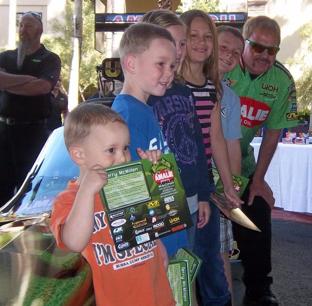 Drag racer Terry McMillen, rear, poses with some young fans at a recent Tahiti Village pit stop.