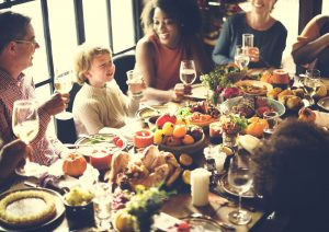 Family at the dinner table enjoy a Thanksgiving meal.