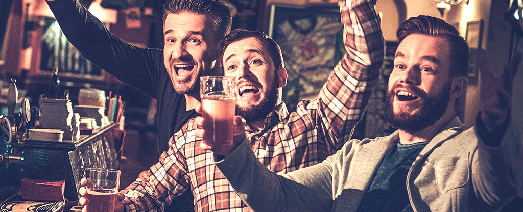 Group of guys enjoying a beer and a game at the bar.