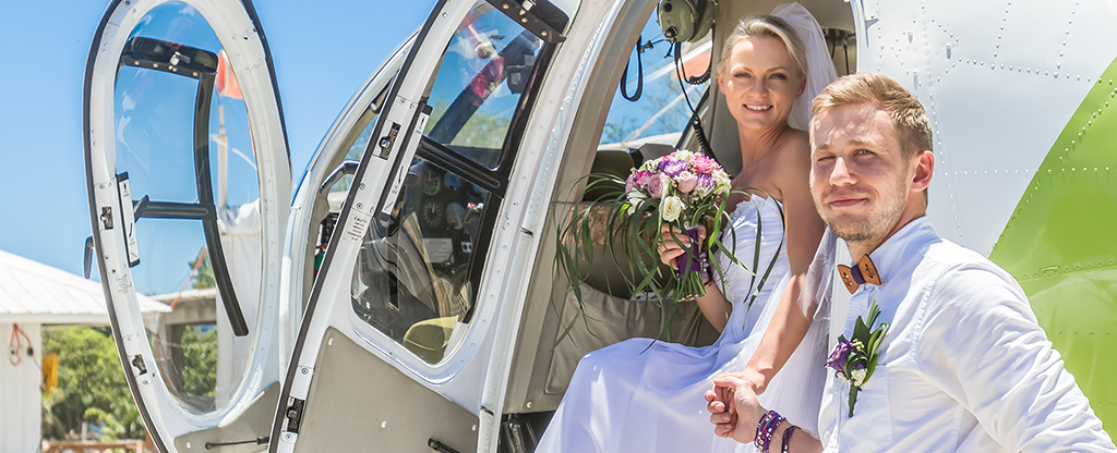 Bride and groom getting ready to go for a helicopter ride.