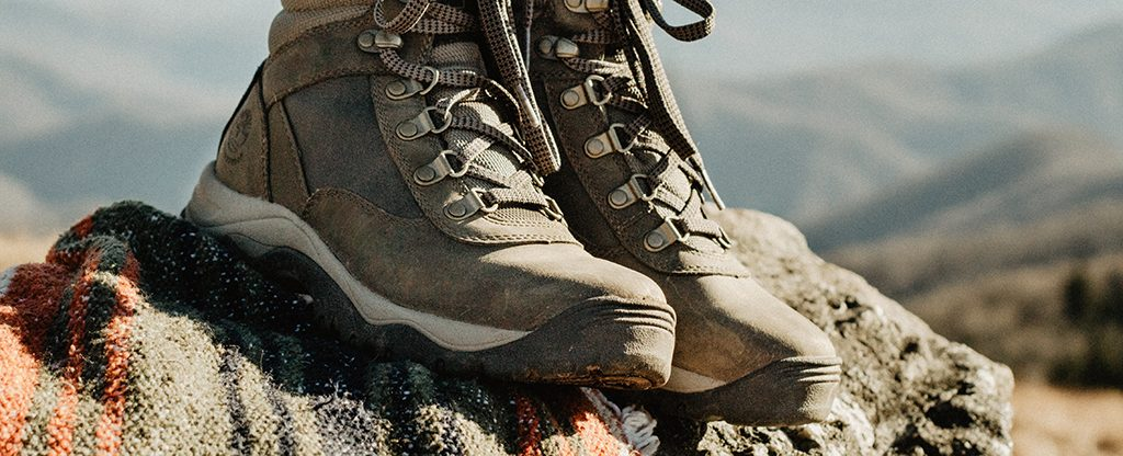Hiking shoes on hiker standing on top of the rocks.