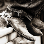 Two pairs of cowboy boots, sitting on the sidelines at the rodeo.