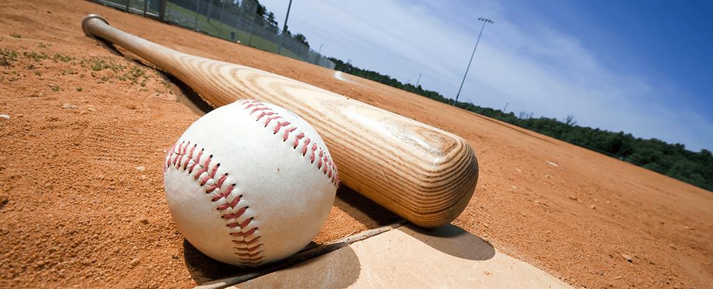Baseball and bat on homebase at the baseball field.