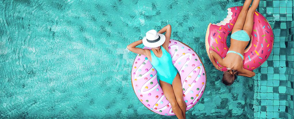 Two women enjoying the pool in donut shaped rafts.