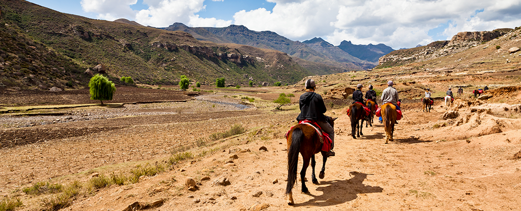 A group of tourists taking a horseback ride tour through Bonnie Spring Ranch in Nevada.